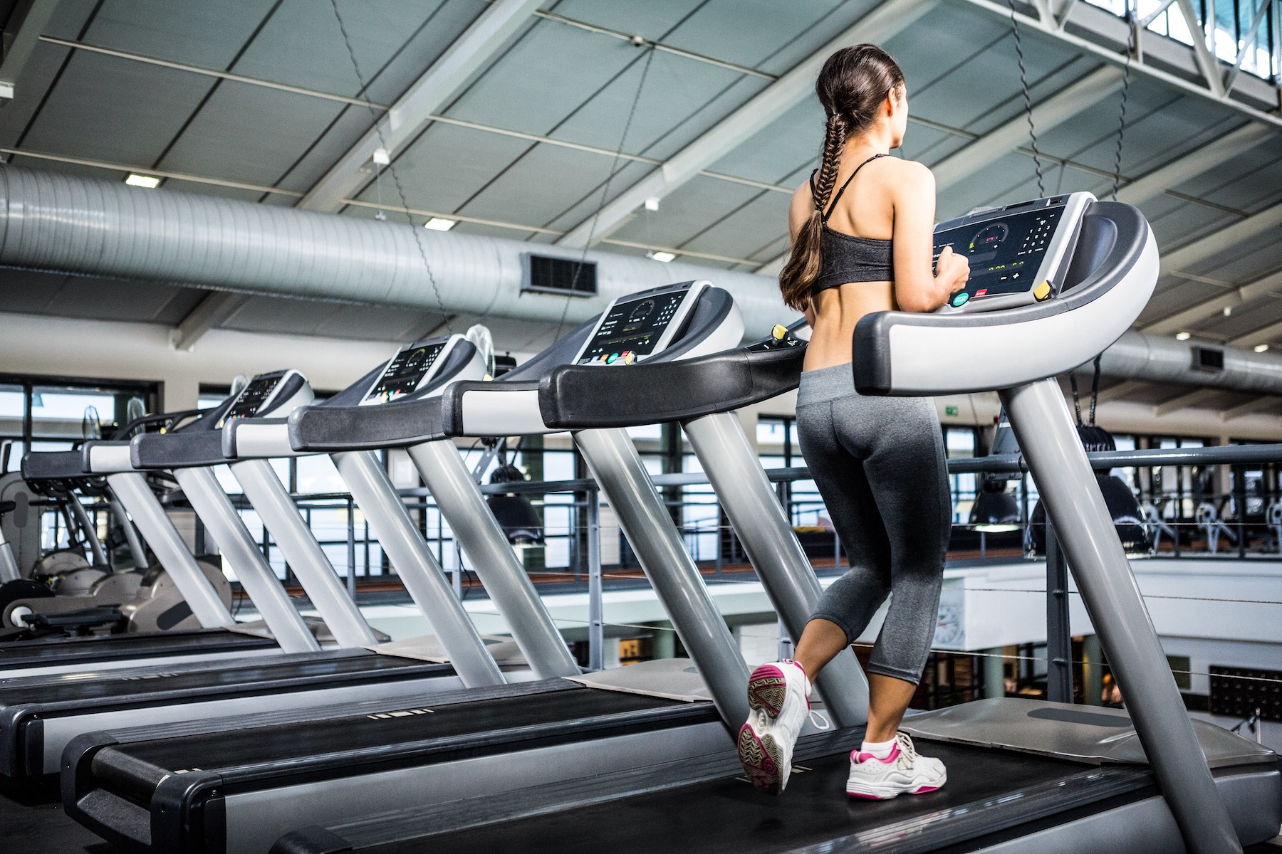 Rear view of woman jogging in treadmill